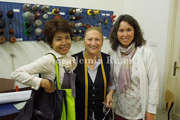 完成したカバンを持った日本人女性生徒と先生と日本語通訳